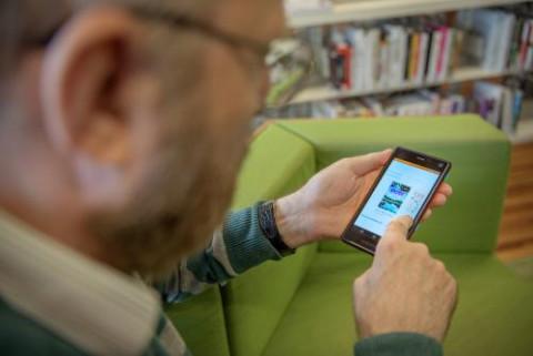 man die bibliotheekwebsite op smartphone bekijkt